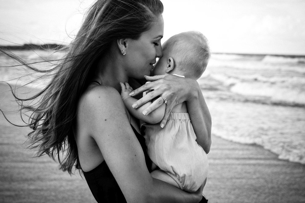 Beautiful and emotional storytelling image of mother with daughter at beach during photography session.