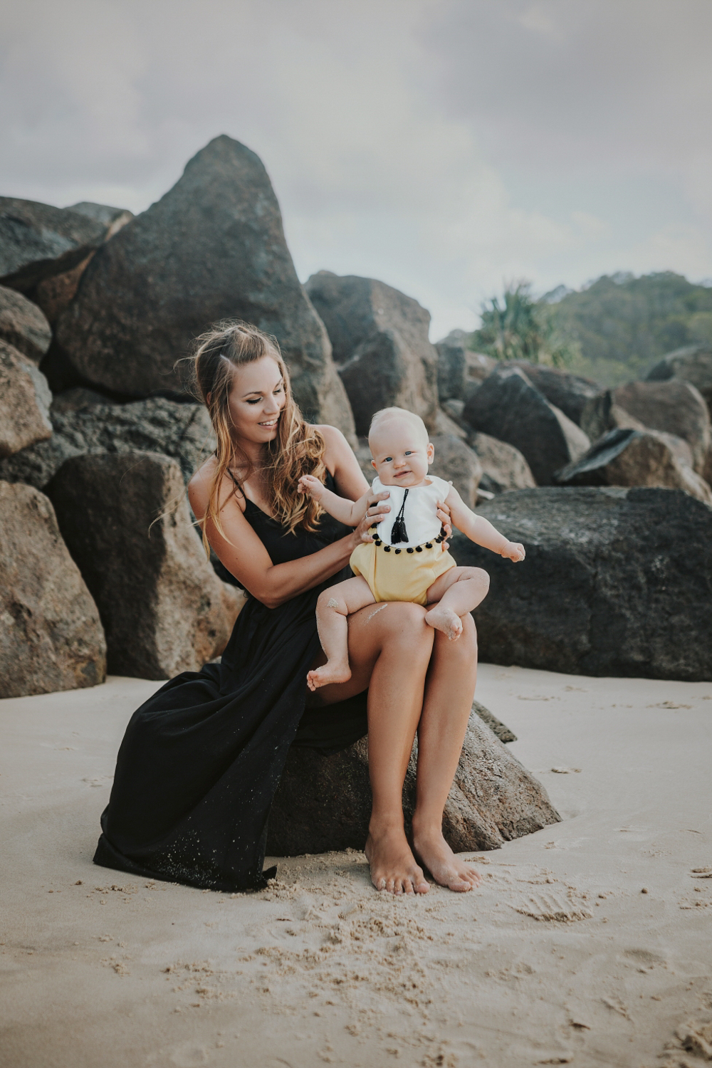 Mother and baby sit on a rock at the beach on the gold coast.