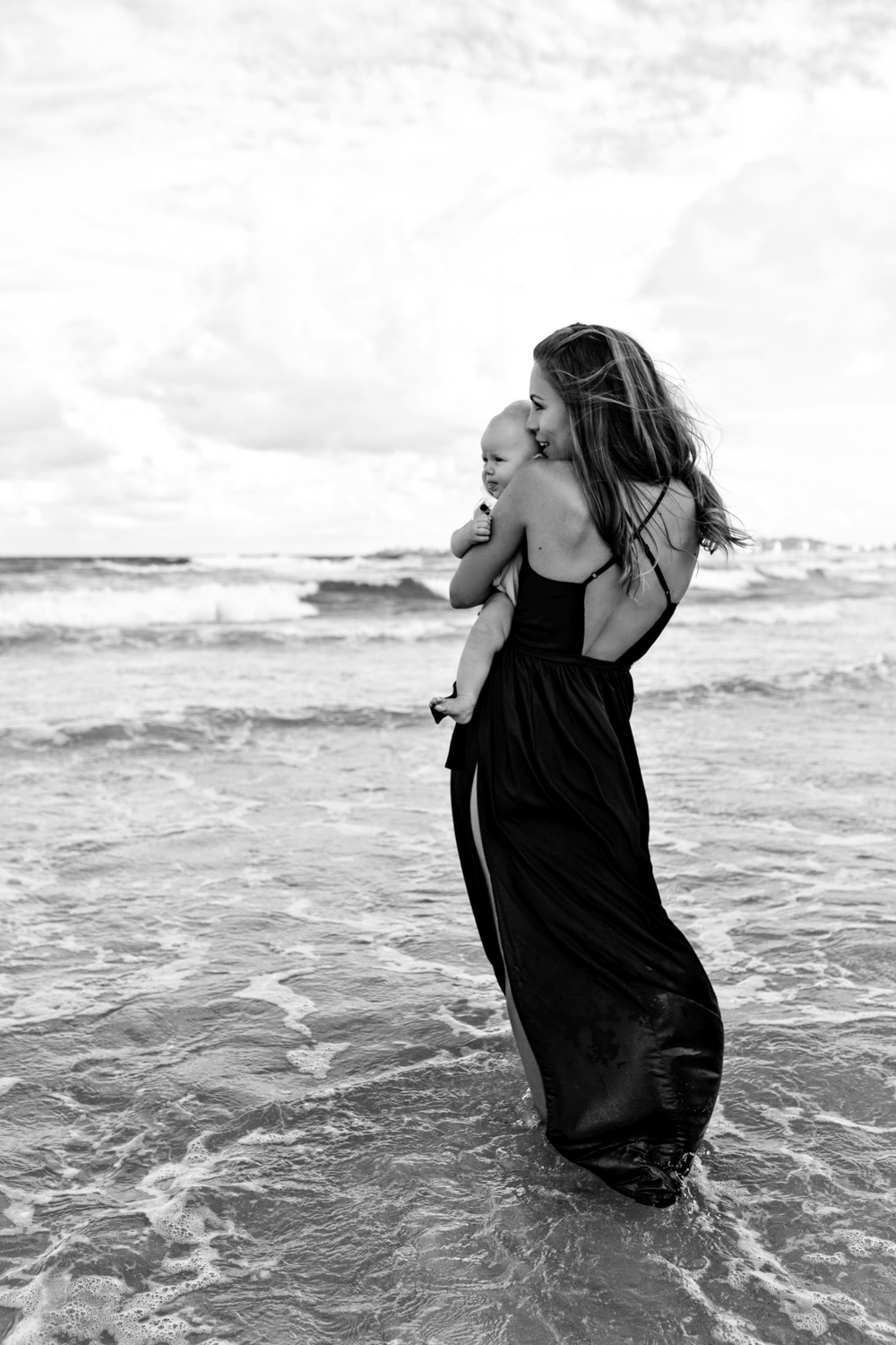Mother and baby wade in the ocean during beach family photography session.