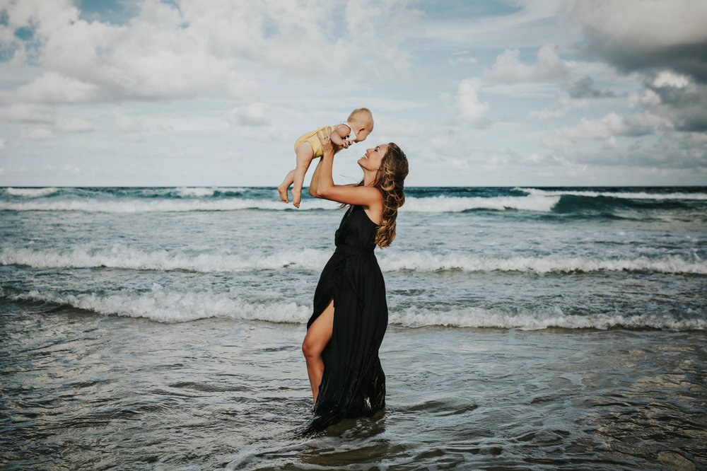 Mother holds baby in air smiling in a natural portrait session on the gold coast.