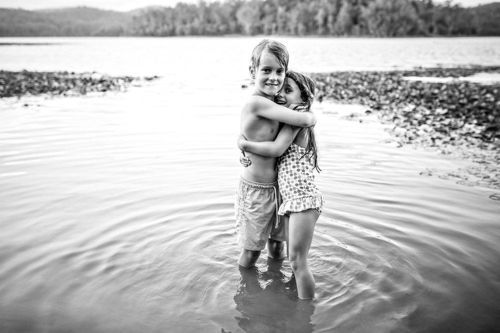 Family session with siblings hugging in the water in Brisbane.