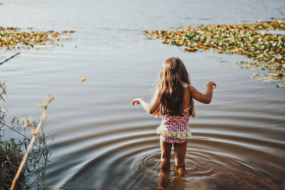 Family photography session with girl entering lake in Brisbane.