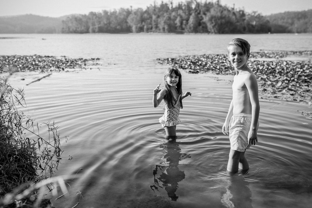 Family photography session with siblings swimming in lake in Brisbane.