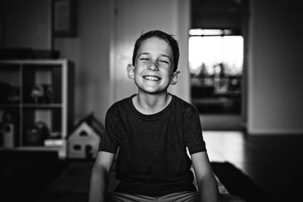 Boy sits and grins widely in family photo session in Queensland.