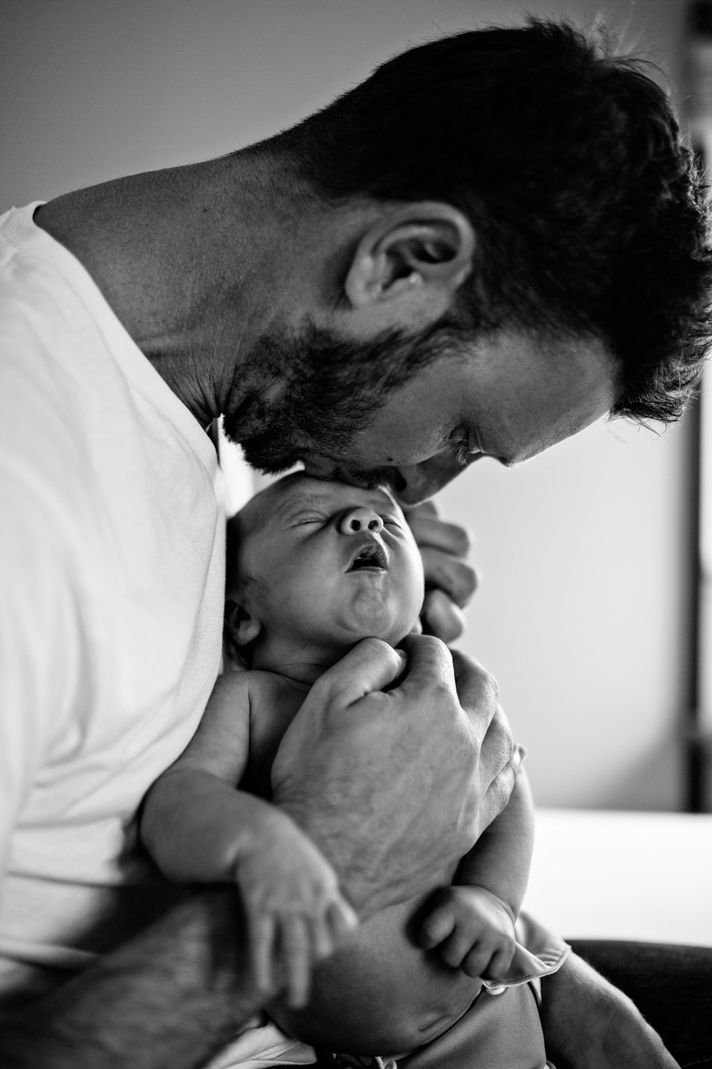 Beautiful image of father kissing newborn son during a home session with newborn baby.