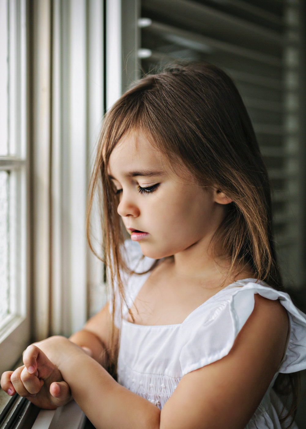 Girl sits peacefully by a window in family session Tasmania.