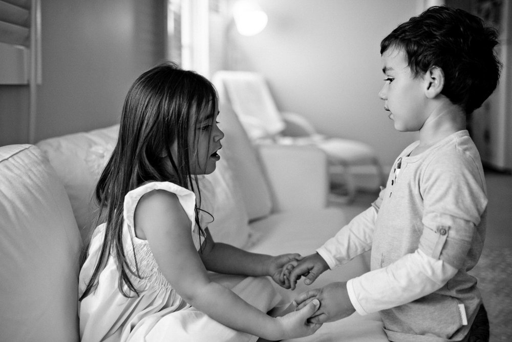 Sister and brother hold hands during family documentary photo shoot.