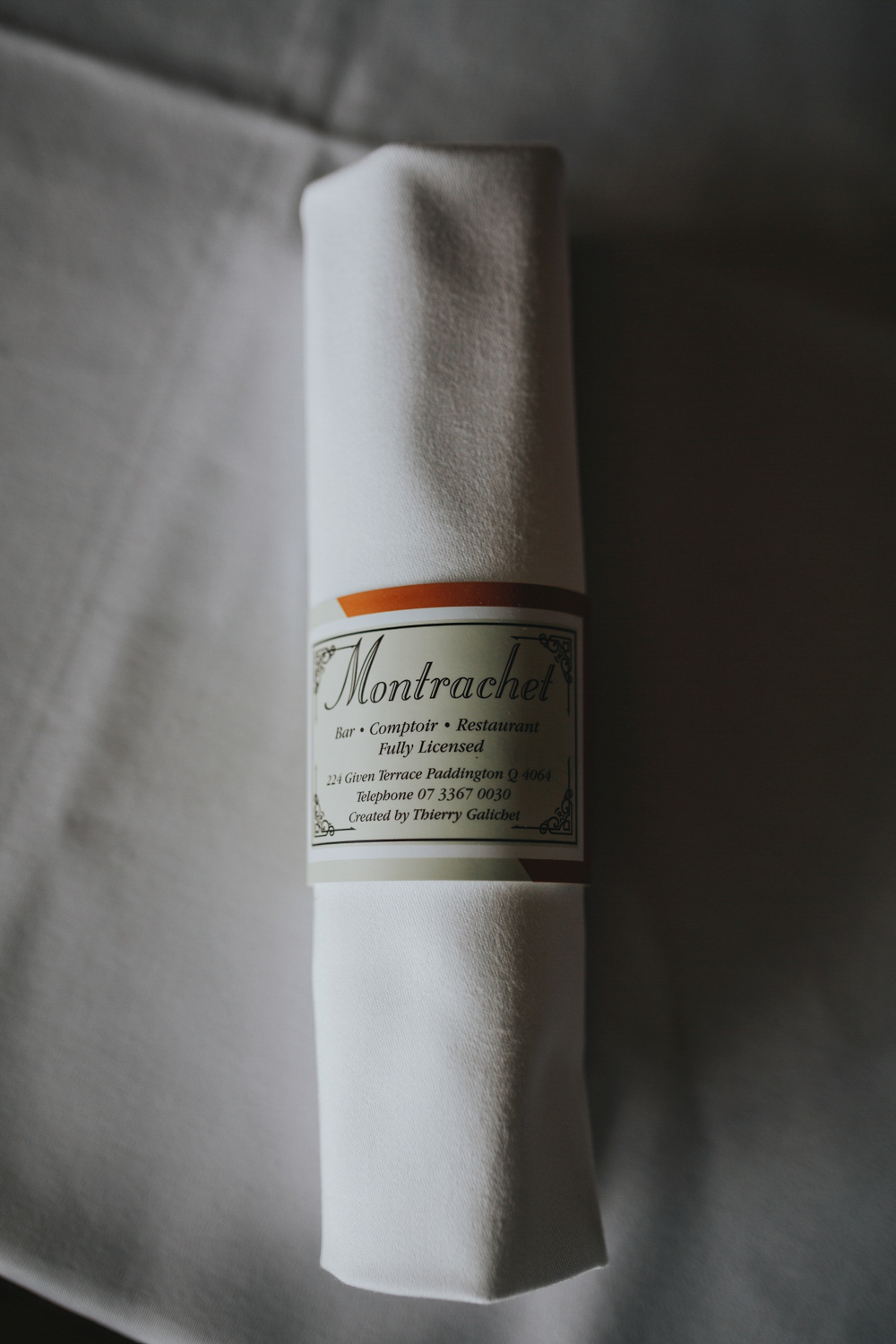 Rustic image of a fine white linen napkin wrapped in branded restaurant napkin holder.
