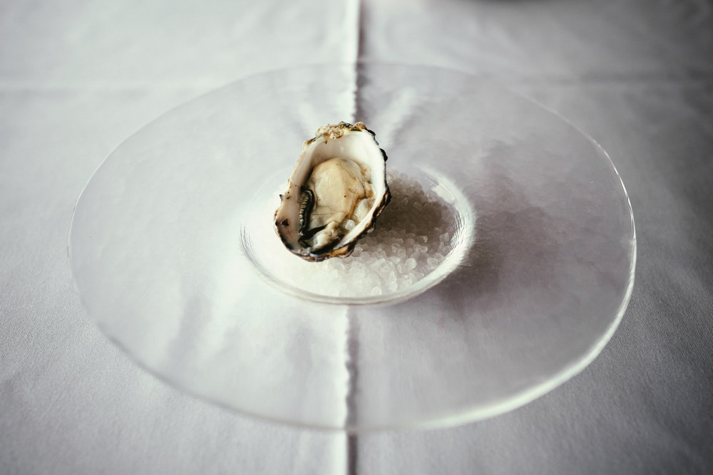 Single oyster rests on a glass plate with salt crystals in fine dining restaurant in Brisbane.