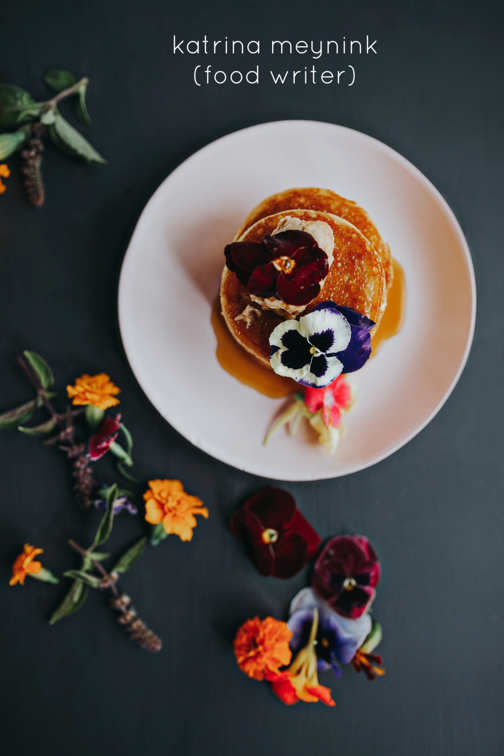 Image of crumpets sitting on a plate with golden honey and bright flowers for katrina meyning food writer.