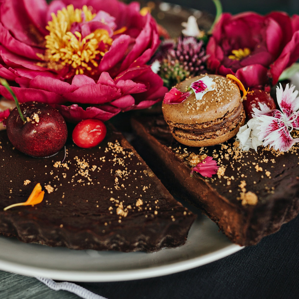 Photo of a beautiful chocolate cake topped with flowers and fruit and caramel macaron.