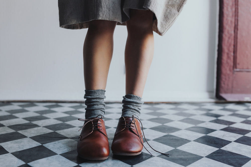 Beautiful image of woman in pair of leather lace up shoes in a photo shoot for the maker hobart.