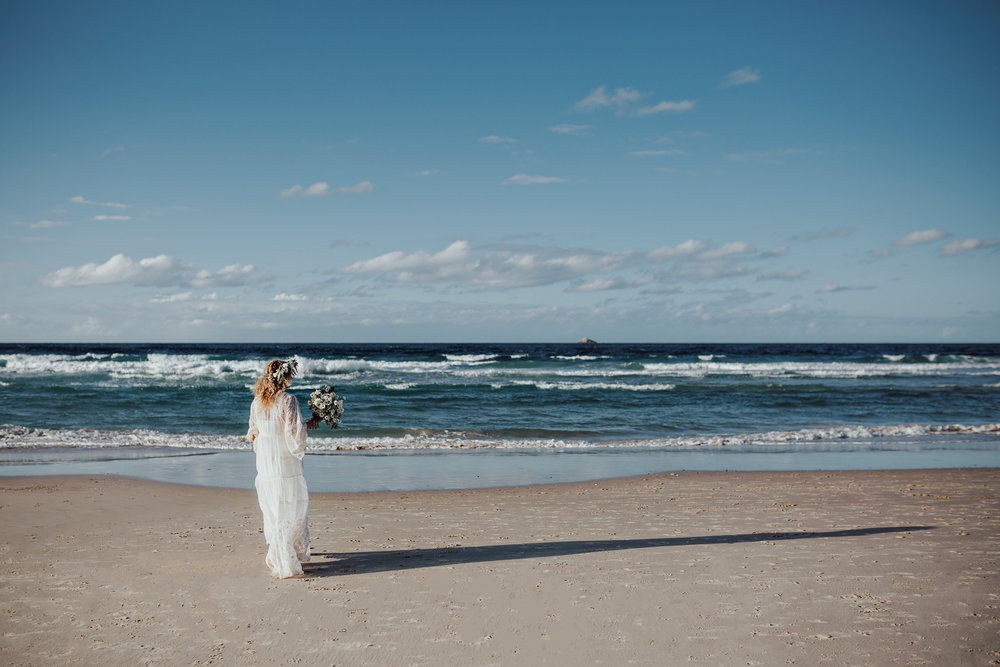 Bride walks toward ocean in Spell Designs gown in Byron Bay.