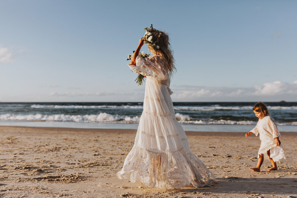 Bride walks with her daughter after relaxed beachside wedding.