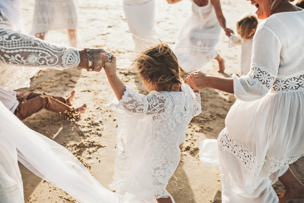 Bridal party enjoy the beach after ceremony in Byron Bay.