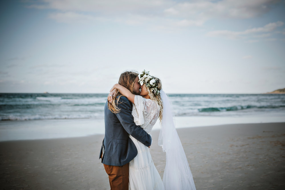 Bride and groom kiss on the beach in boho wedding.