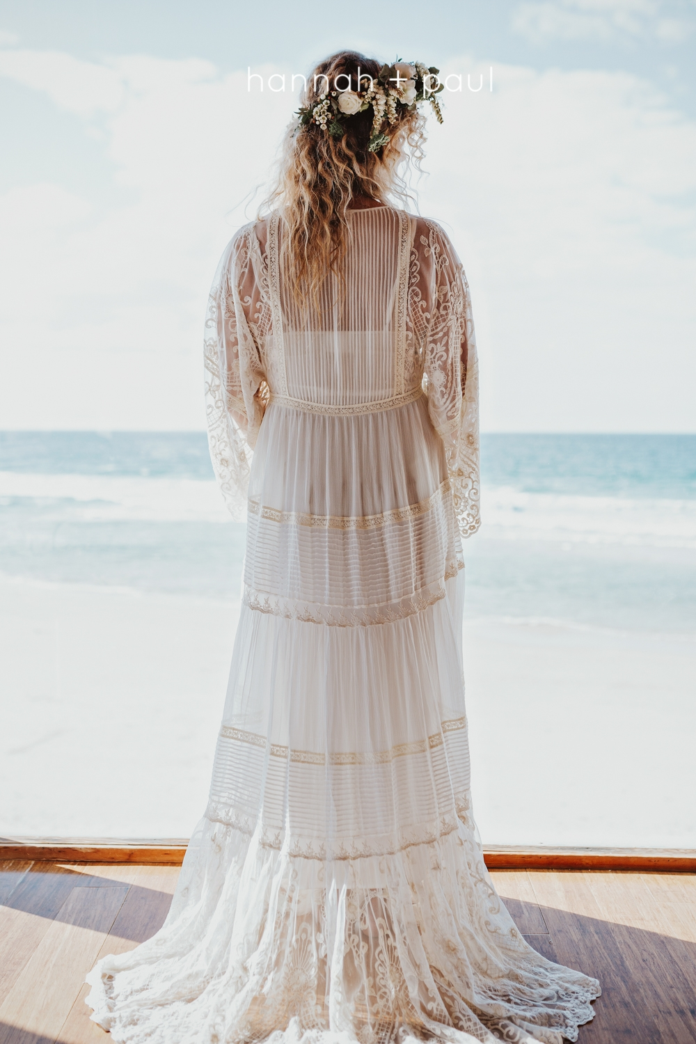 Bride stands at window by the sea in Byron Bay wedding.