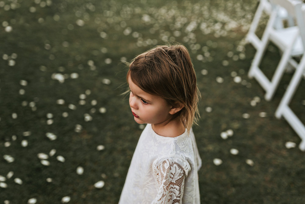 Flower girl stands with petals after wedding ceremony.