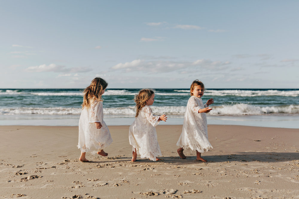 Flowergirls play at beach in boho relaxed Byron wedding.