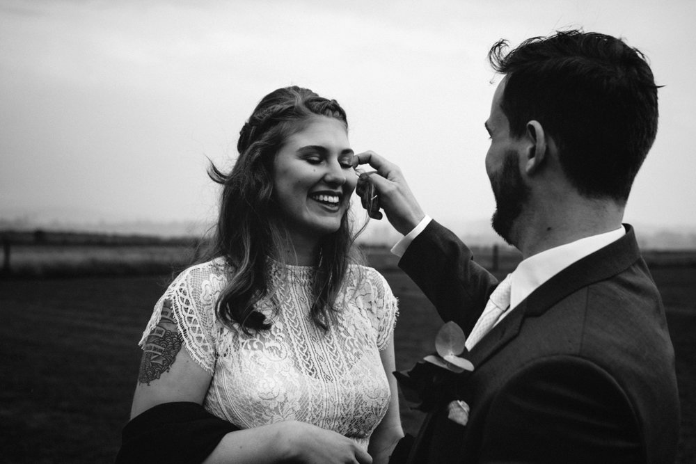 Groom adjusts hair from brides face during couple portraiture at a wedding in northern tasmania.