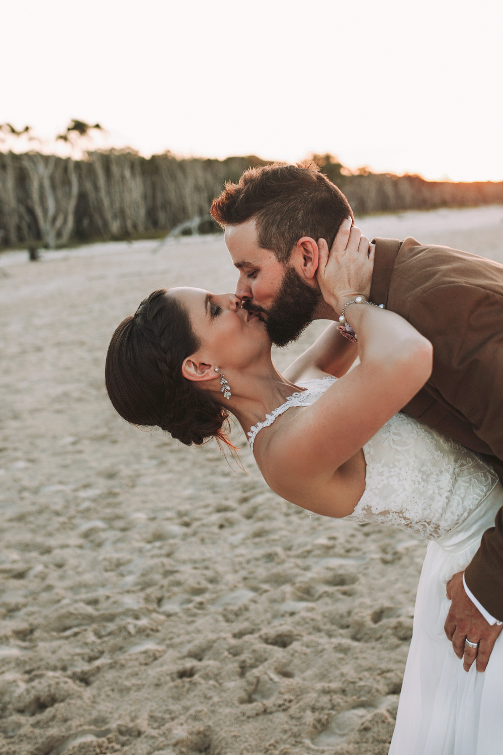 bride and groom kiss after their ceremony on the beach.