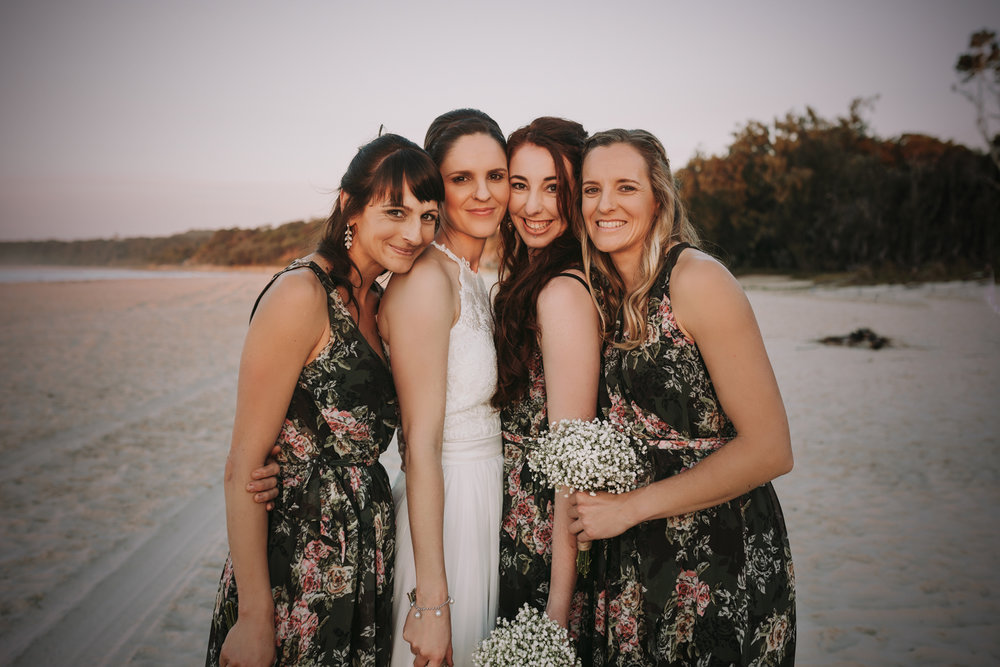 bridesmaids hug on the beach at sunset on stradbroke island