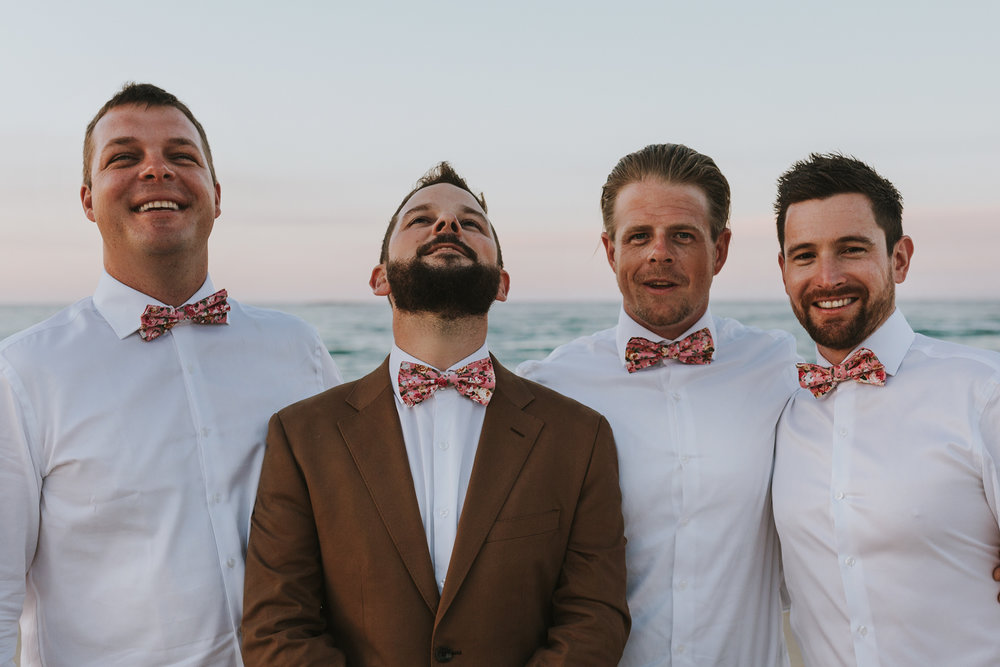 Groomsmen show off their handmade bow ties at the beach.