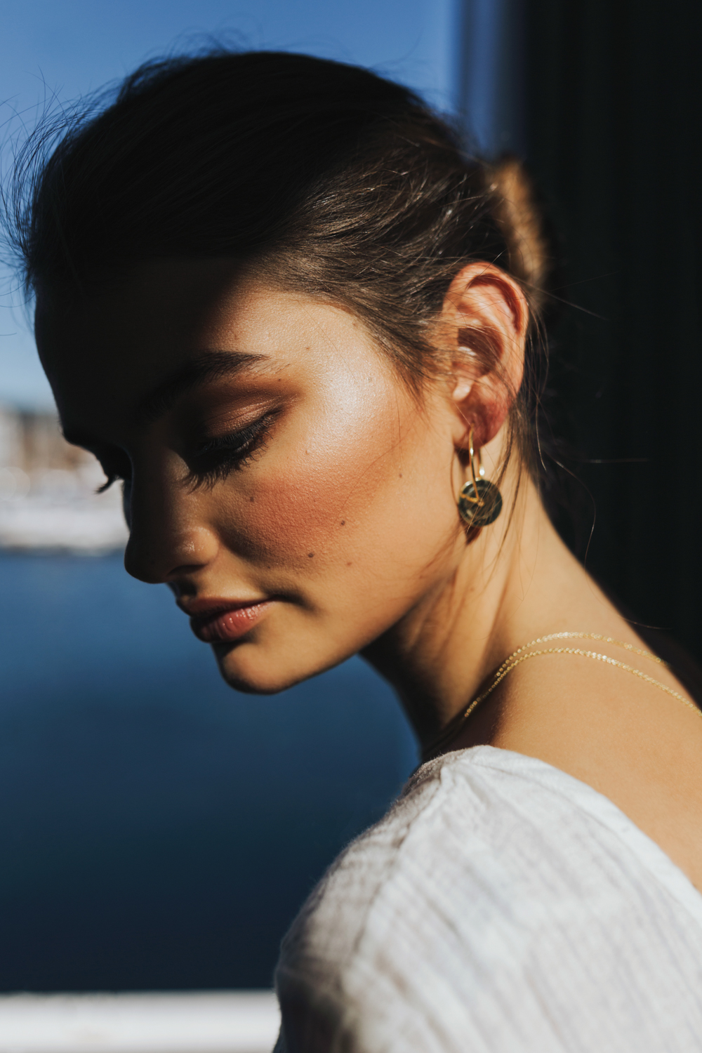 Model poses in sun and shadow with gold jewellery.