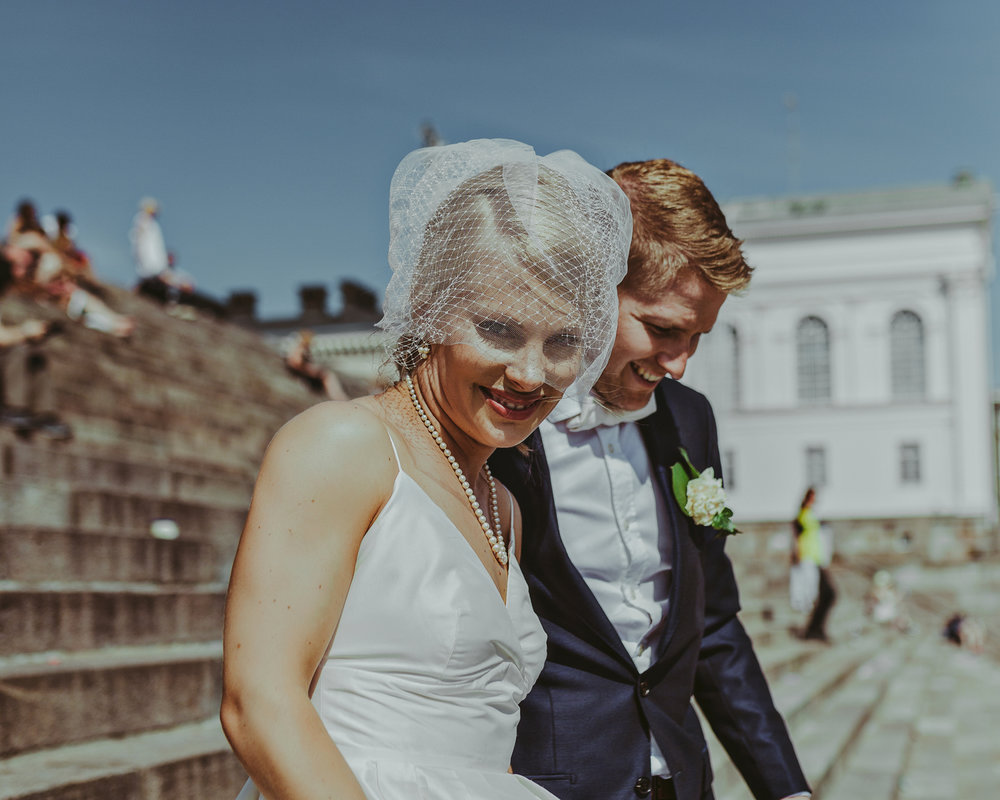 Bride and groom walk down steps in Helsinki wedding.