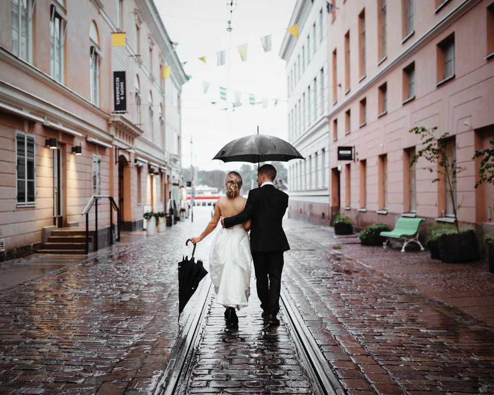 Newlyweds walk down rainy cobblestone street in Finland.