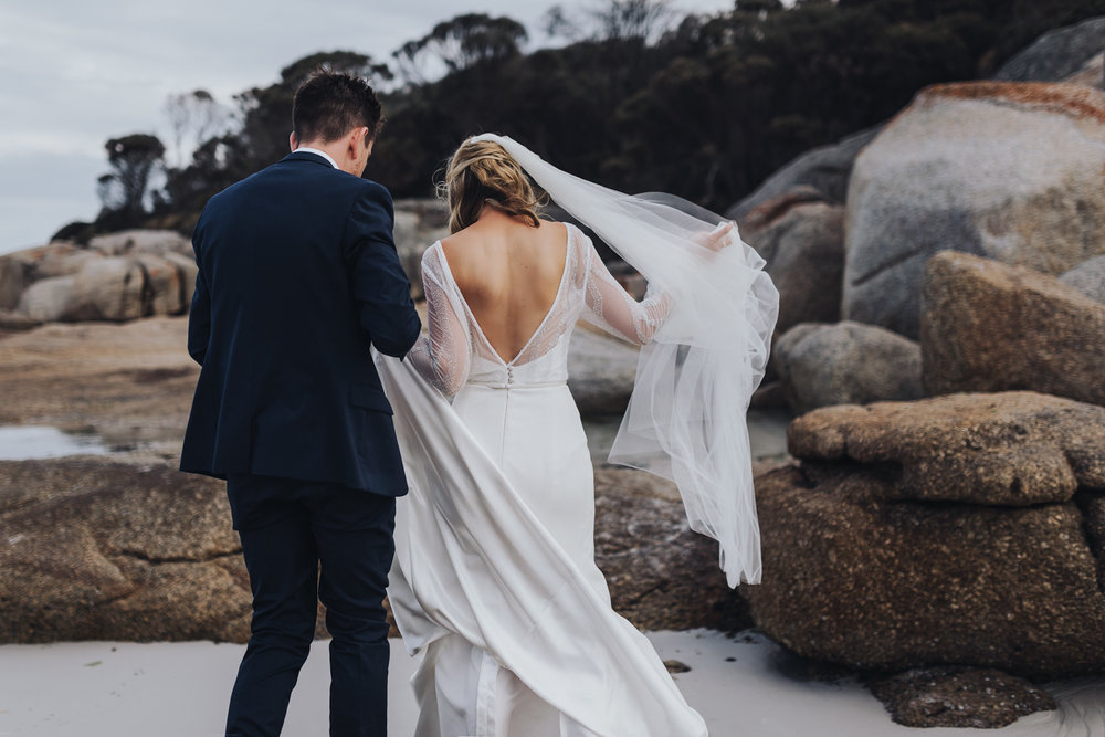 Bride and groom walk on beach at Bay of Fires wedding in Tasmani