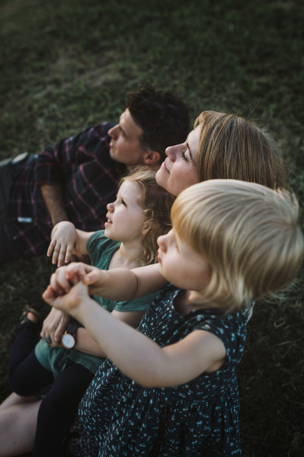 Family enjoy relaxing outside during beautiful family photo sess