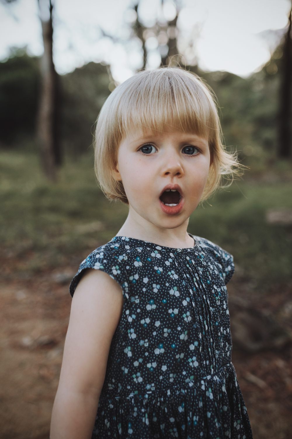Child with sweet expression stands in nature during casual photo