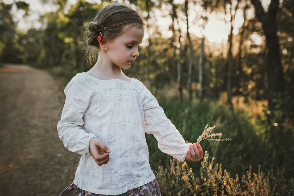 Girl picks plants during nature based photo session.
