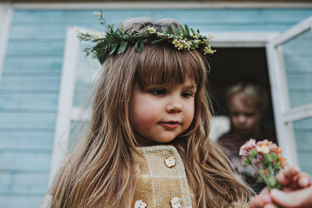 Young girl stands with posy of flowers and flower crown on her h