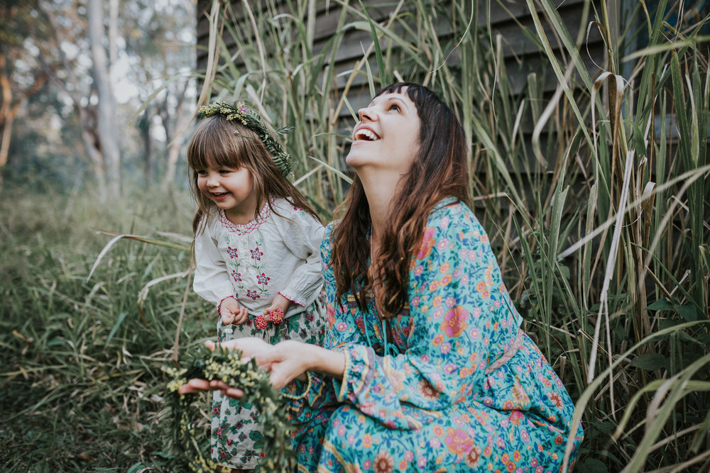 Mother and daughter laugh in the grass during photo session.