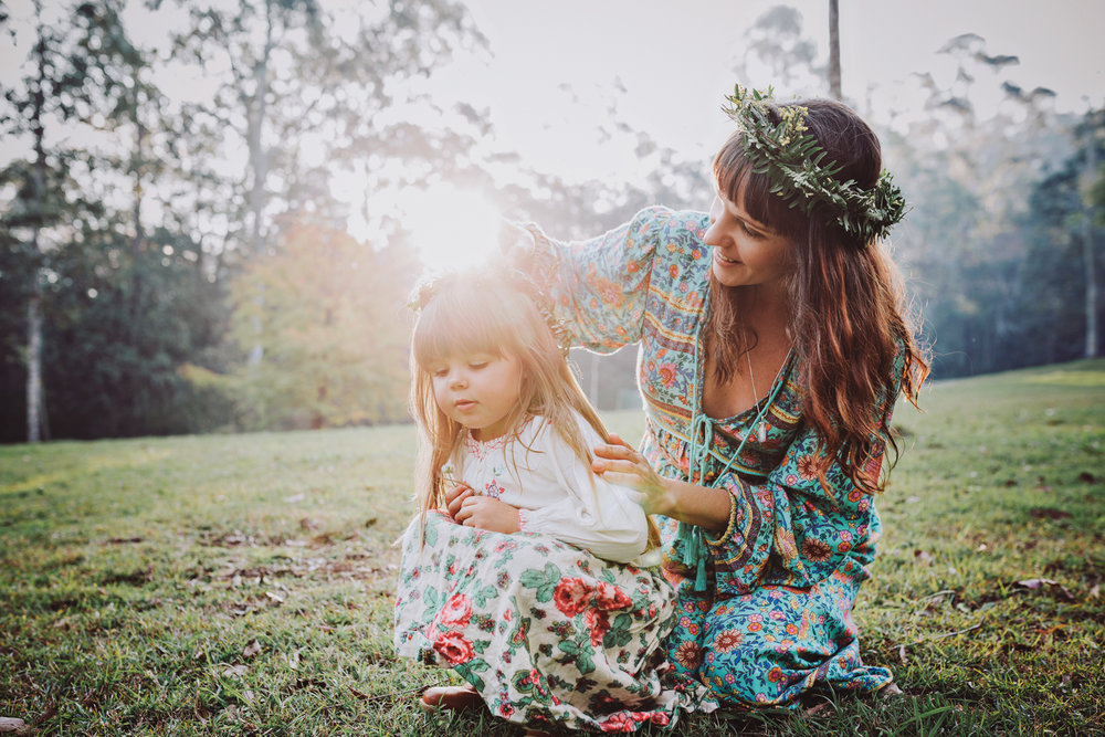 Mother adjusts daughter's flower crown during beautiful sunset p