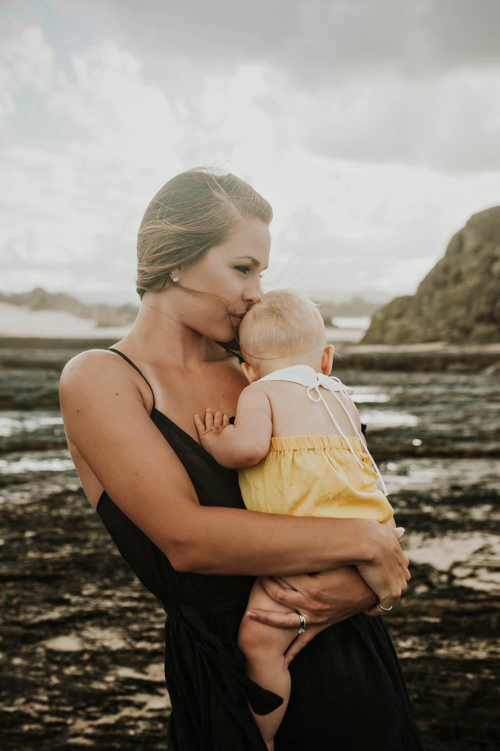 Mother embraces with her baby daughter during beautiful beach ph