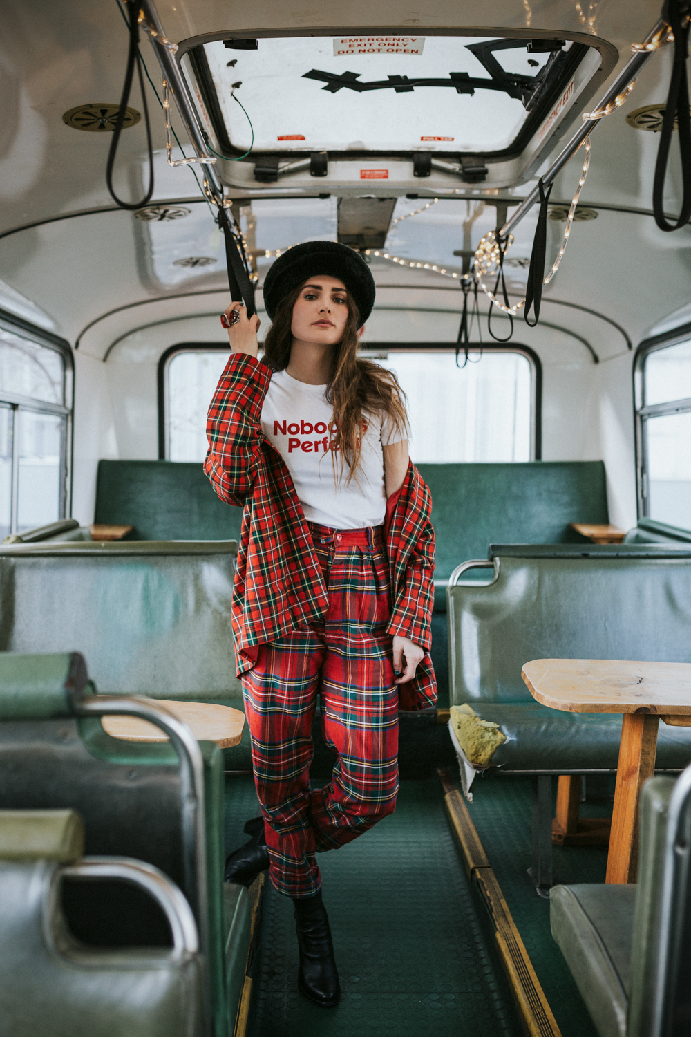 Model stands in bus for vintage fashion photo shoot.