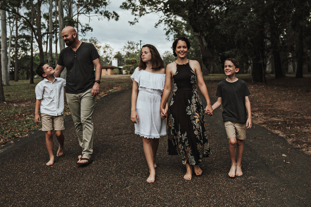 Family walk down street barefoot during relaxed photo session.