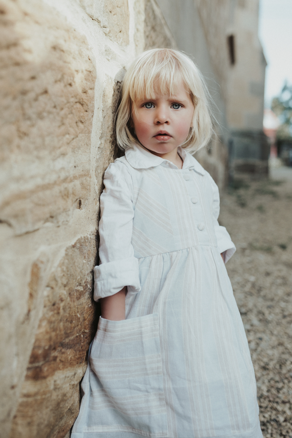 Blonde girl stares into camera by sandstone wall.
