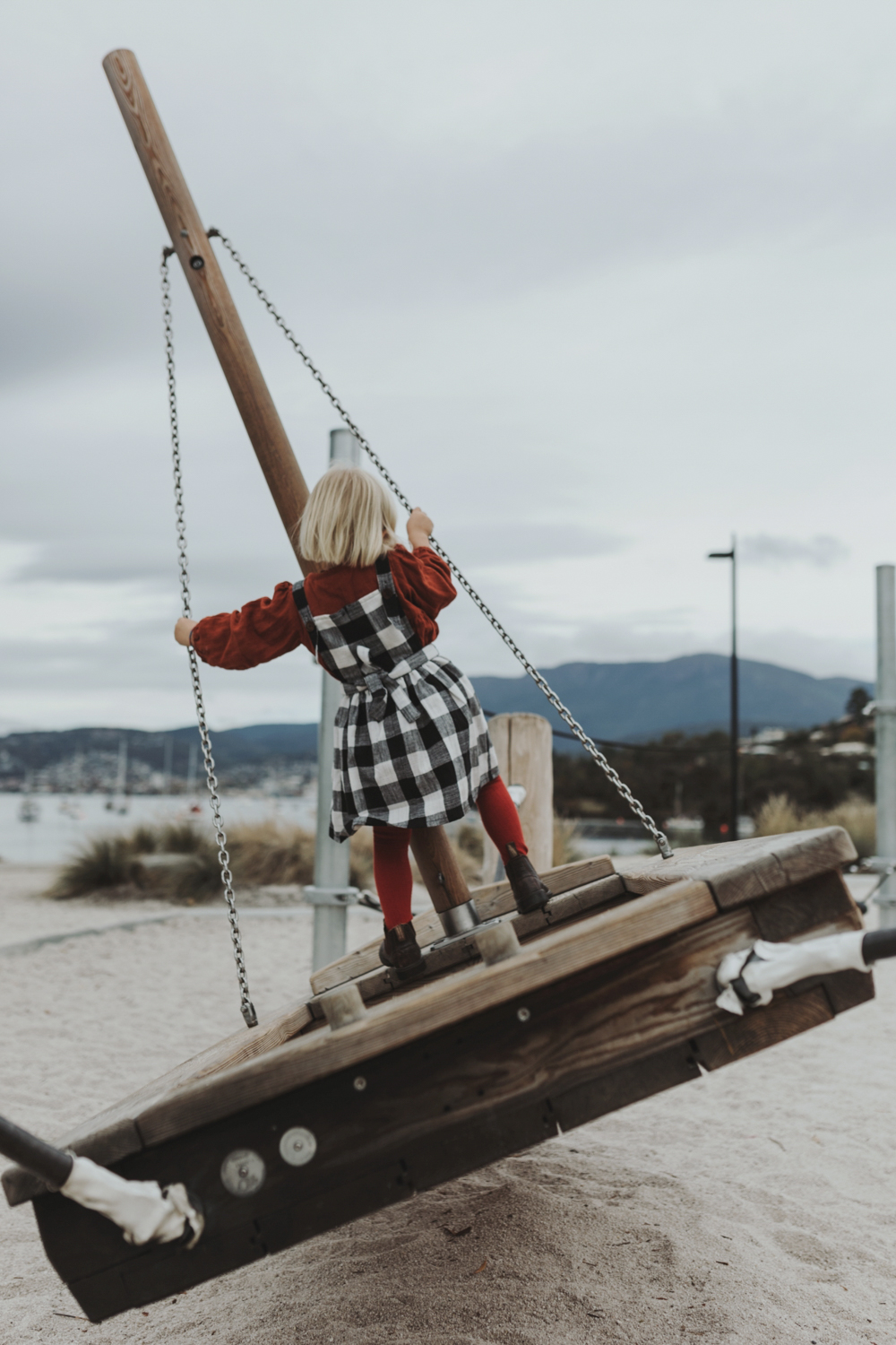 Girl rocks sail boat wearing plaid dress.