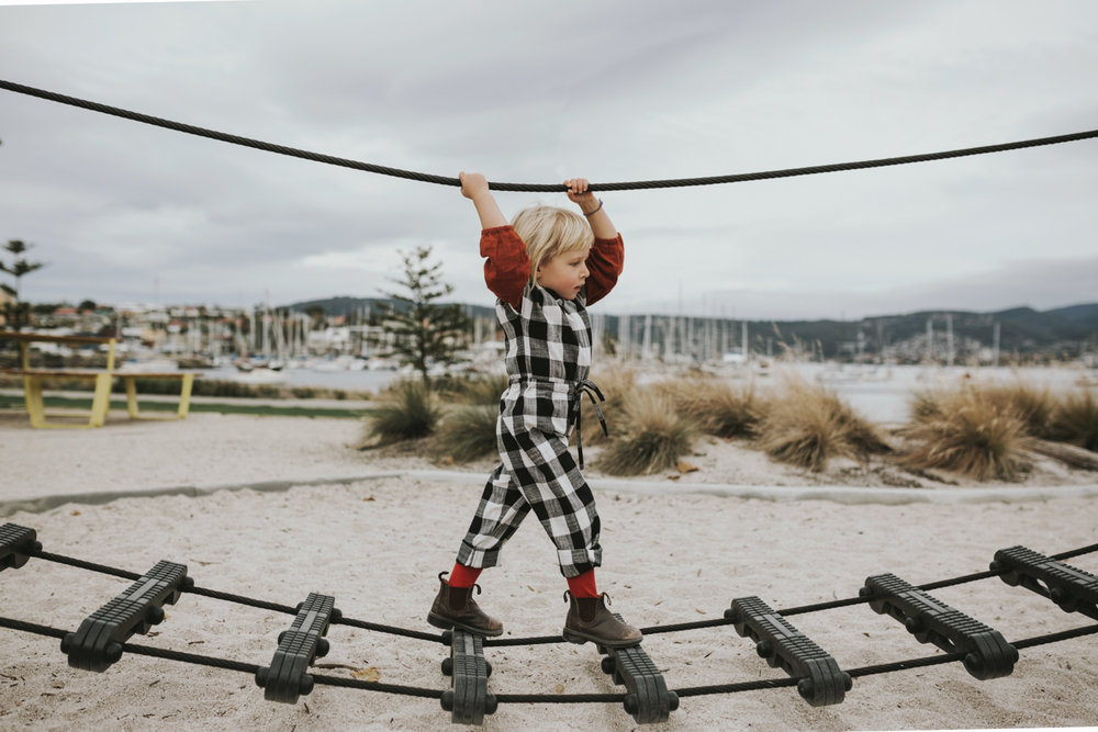 Girl plays on playground equipments in Hobart for photoshoot by