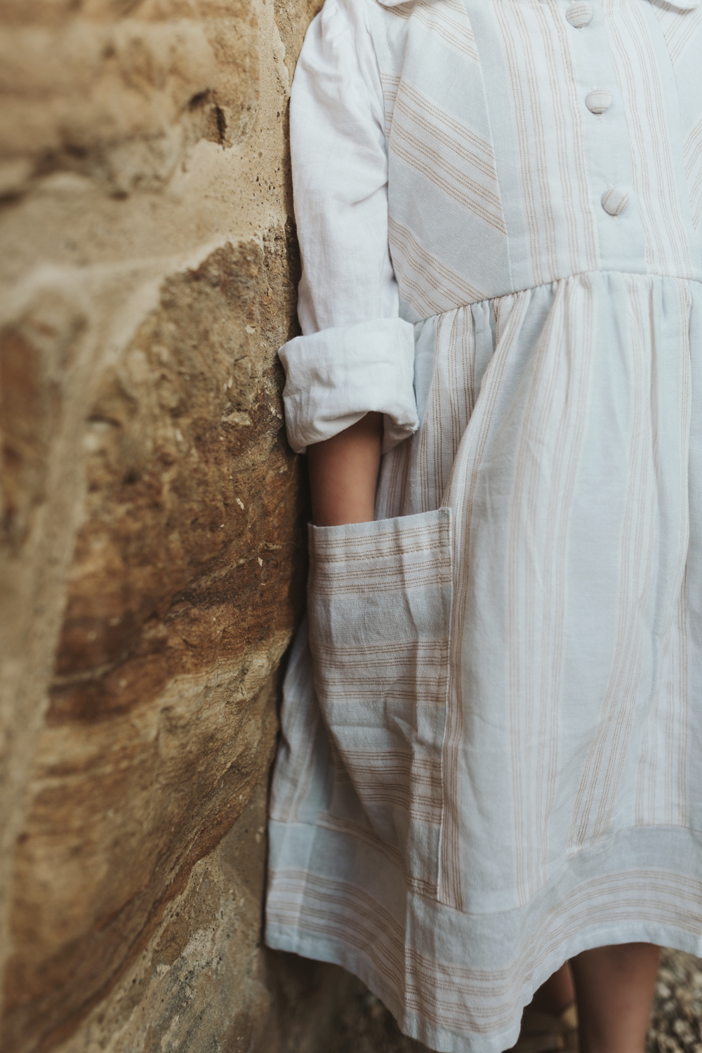 Detail shot of cotton dress pocket next to sandstone wall by Sii