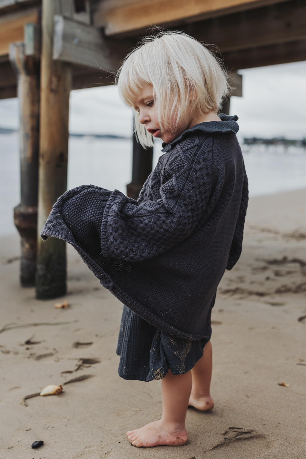 Girl looks into her pocket at the beach in Tasmania.