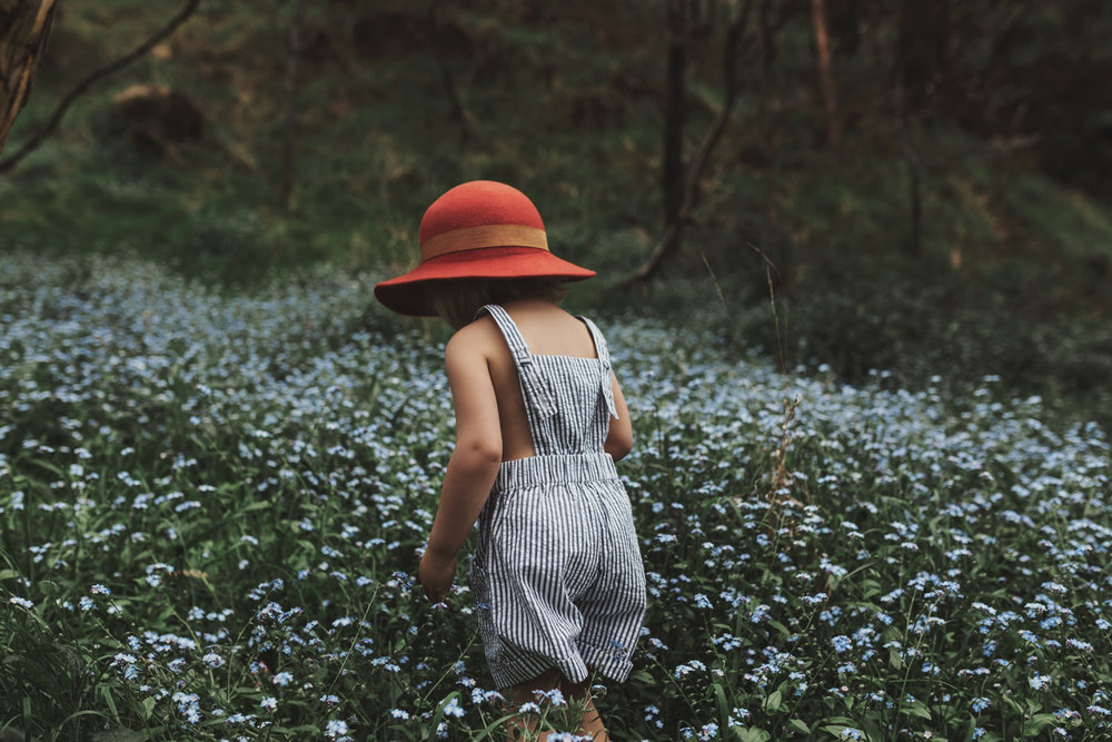 Girl walks in field of blue flowers with red felt hat for Minouc