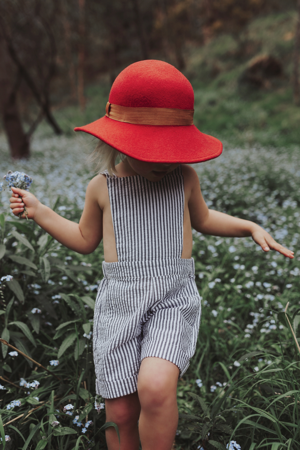 Young girl walks through field of flowers in beautiful photo sho
