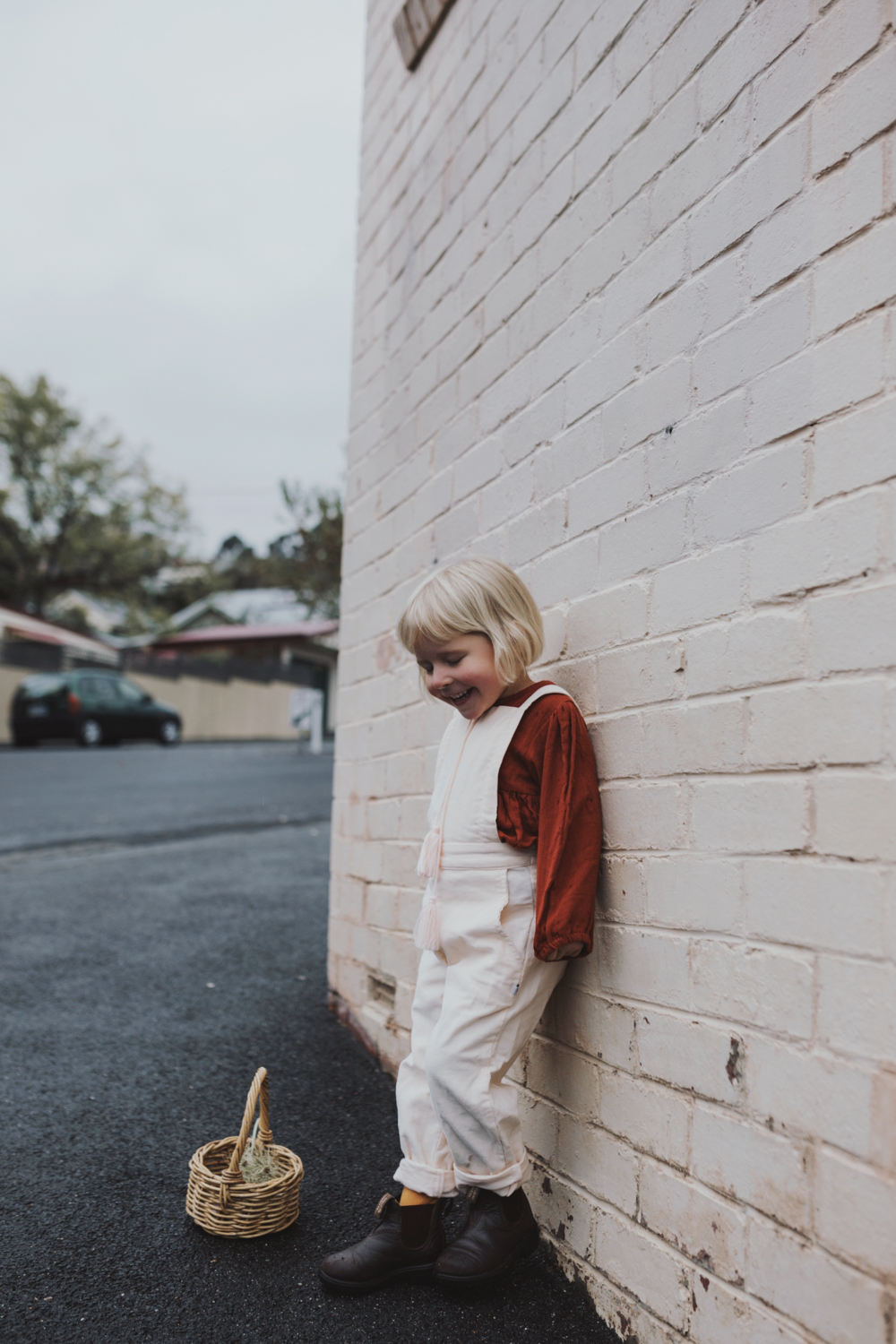 Girl smiles against pink brick wall with little basket.