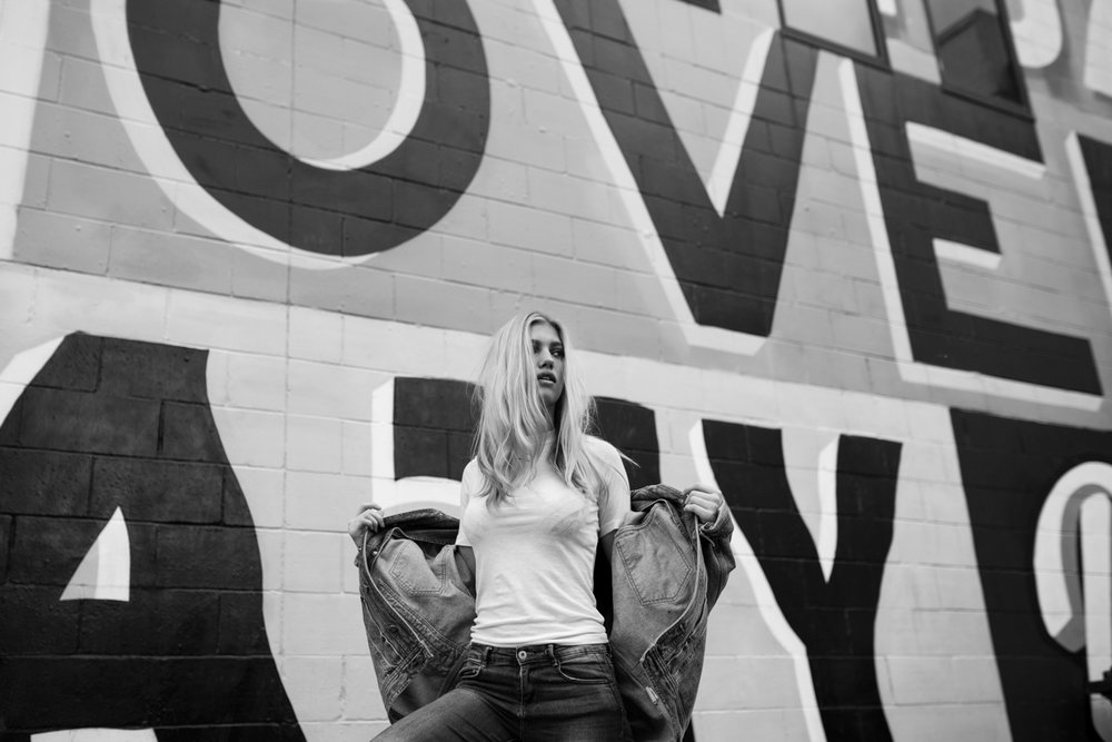 Black and white image of blonde model in front of wall with stre