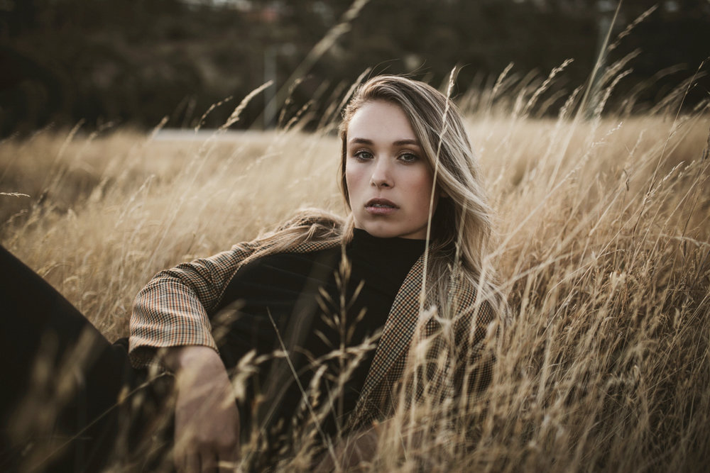 Fashion model lies in grass during photo shoot in Hobart Tasmani